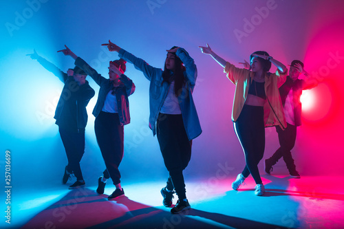 In de dag Dance School Young modern dancing group of six adult young people practice dancing on colorful background