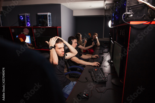 Fotomural Young female and male gamers playing video game while spending weekend leisuretime at pc gaming club, focused serious people behind pc monitor at dark room