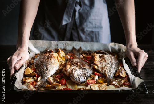Fototapeta fish for dinner. in female hands baked fish on a baking sheet. obraz