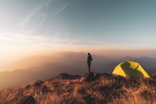 Young Man Traveler Looking Landscape At Sunset And Camping On Mountain, Adventure Travel Lifestyle Concept