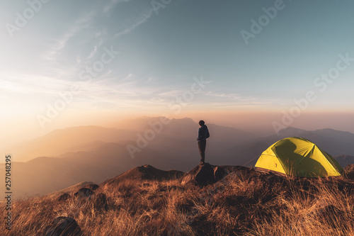 Foto Young man traveler looking landscape at sunset and camping on mountain, Adventur