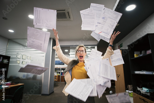 Obraz Stressed woman throws papers in the office in an image of relief - fototapety do salonu