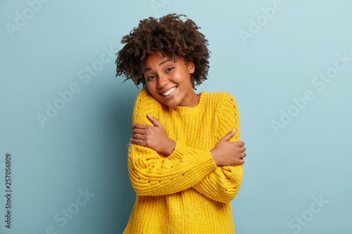 Fotografia  Headshot of pleased dark skinned woman hugs herself, smiles from pleasure, likes