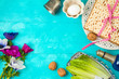 Jewish holiday Passover background with matzo, seder plate and spring flowers on wooden table.