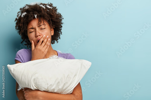 Fotografie, Obraz  Sleepy tired young Afro American woman covers mouth with hand, yawns after sleep, embraces white pillow, has feathers in head, poses over blue background with blank space for your promotion