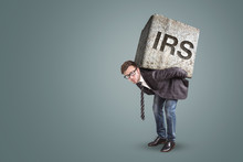 Businessman Carrying A Heavy Stone With The Letters IRS On It