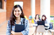 Headshot of young happy attractive asian student smiling and looking at camera with friends on outdoor university background. Asian woman in self future education or personalized learning concept.