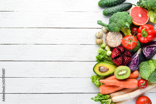 Poster Cuisine Fresh vegetables and fruits on a white wooden background. Healthy Organic Food. Top view. Free copy space.