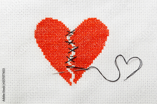 The broken red heart is threaded with black threads Canvas Print