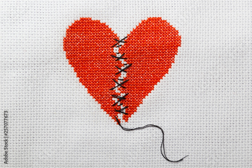 The broken red heart is threaded with black threads Wallpaper Mural