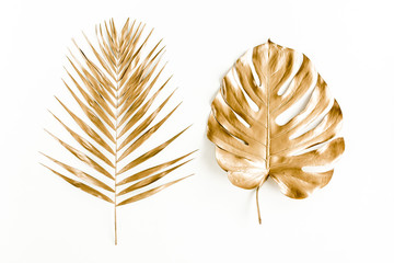 Gold tropical palm leaves Monstera on white background. Flat lay, top view minimal concept.