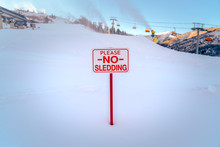 Please No Sledding Sign Against Snow And Ski Lifts