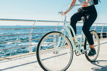 Young Woman Riding Vintage Bike Along The Waterfront