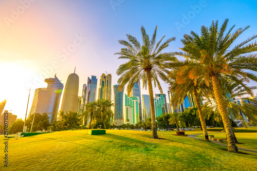 Fényképezés  Palm trees in West Bay park along corniche promenade with glassed high rises at sunset on background