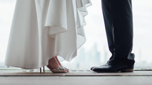 The Legs Of The Bride And The Feet Of The Groom