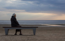 Old Lonely Retired Grandmother Sitting On A Bench
