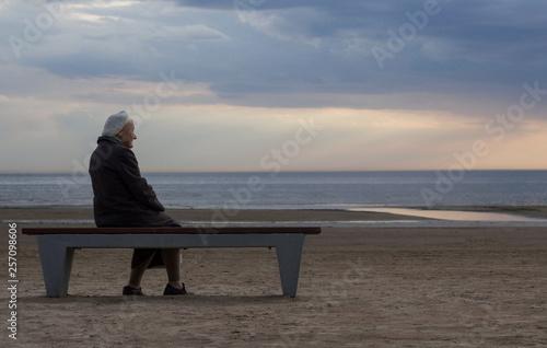 Obraz na płótnie old lonely retired grandmother sitting on a bench