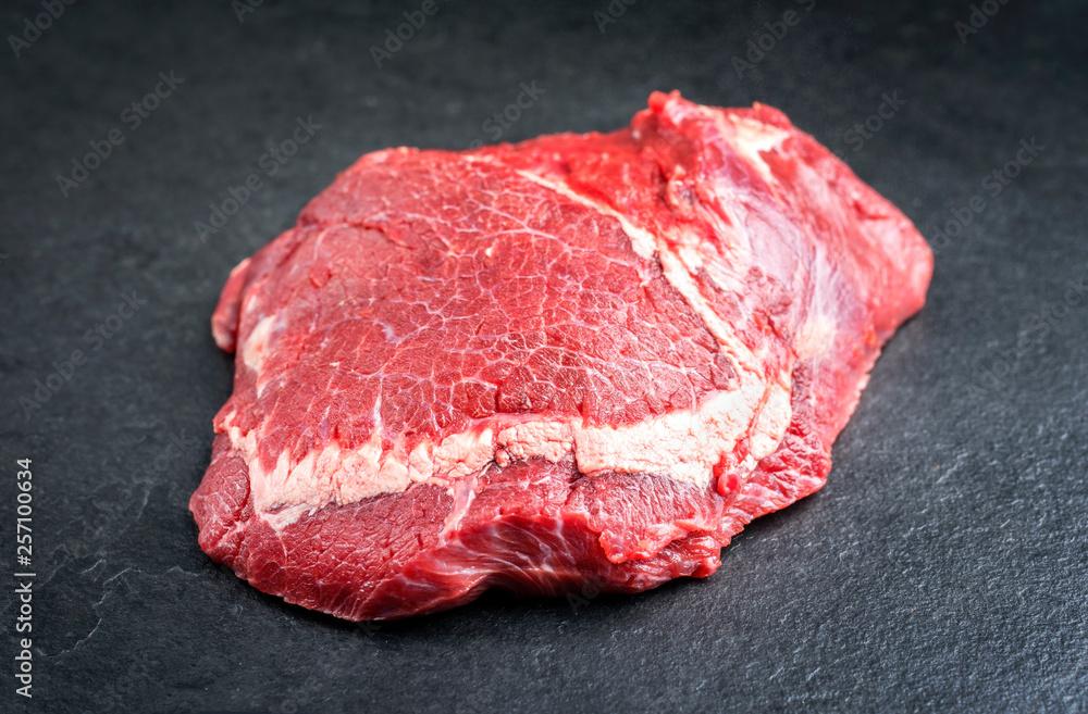 Fototapeta Traditional raw beef cheeks as closeup on a black board