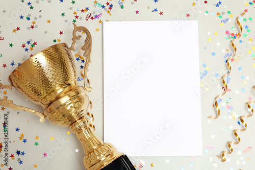 Fotografía  Trophy and blank paper on light background, top view with space for text