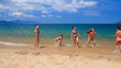 cheerleaders in bikinis perform hand scale stunt on wet sand