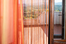 Romantic Terrace Patio Garden Outside In Italy In Tuscany And Blinds Strings With Red Orange Color On Open Door Doorway Fringe Tassel