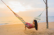 Portrait beautiful young asian woman sitting on the hammock with smile happy neary beach sea and ocean