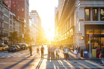 NEW YORK CITY, CIRCA 2018: Bright light of sunset shines on crowds of people crossing the intersection on 5th Avenue in Manhattan, New York City