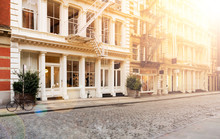 Sunlight Shines On The Empty Sidewalks Along Cobblestone Covered Greene Street In The SoHo Neighborhood Of Manhattan In New York City