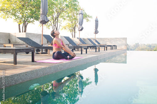 Fotografia  Healthy asian woman doing yoga at the poolside, roof top of hotel with beautiful