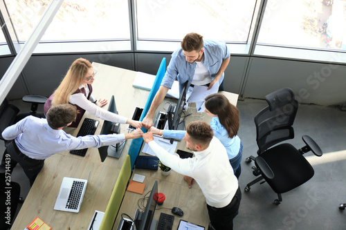 Fototapeta Top view of young modern colleagues in smart casual wear working together while spending time in the office. obraz na płótnie