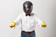 Studio Image Of Stylish Elderly Driver Wearing White Shirt, Jeans, Red Bow, Yellow Gloves And Protective Motorcycle Helmet Keeping Clenched Fists As If Holding Handle Bar, Riding Invisible Motorcycle
