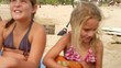 A family sits in the sand and plays instruments