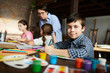 Portrait of cute little boy looking at camera while painting pictures in art class, copy space