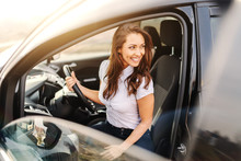 Gorgeous Caucasian Woman With Brown Hair And Toothy Smile Getting Out Of Car.