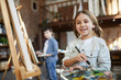 Waist up portrait of cute little girl painting picture on easel in art class and holding palette, copy space