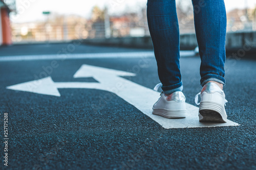 Obraz Make decision which way to go. Walking on directional sign on asphalt road.  - fototapety do salonu
