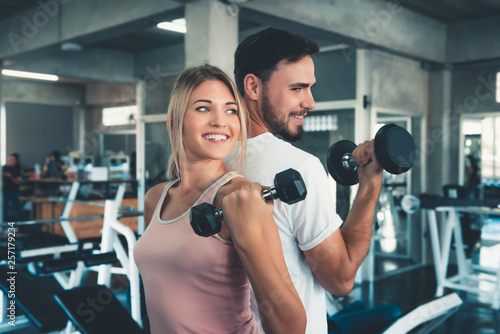 Tuinposter Fitness Portrait of Couple Love in Fitness Training With Dumbbell Equipment., Young Couple Caucasian are Working Out and Training Together in Gym Club., Sport and Healthy Concept.