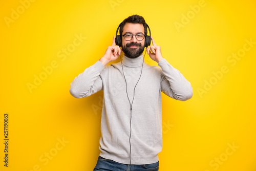 Fotografie, Obraz  Man with beard and turtleneck listening to music with headphones