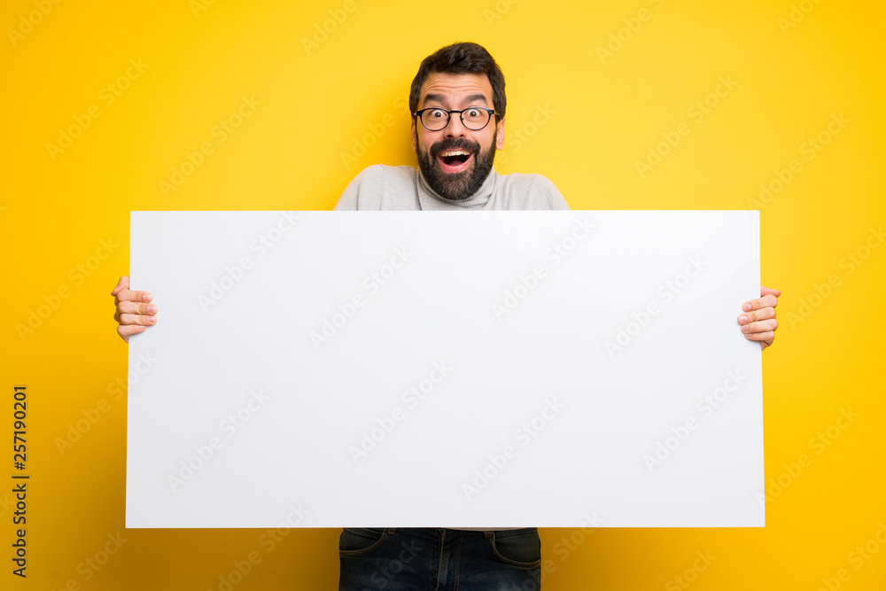 Fototapeta Man with beard and turtleneck holding a placard for insert a concept