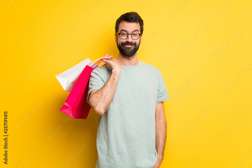 Fototapeta Man with beard and green shirt holding a lot of shopping bags