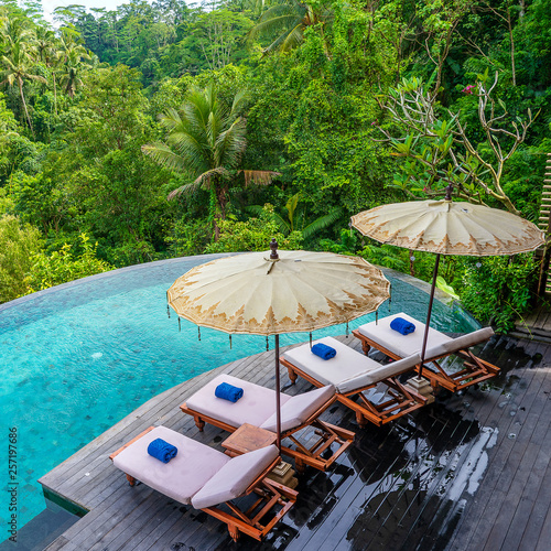 Tableau sur Toile View of the swimming pool water and sunbeds in the tropical jungle near Ubud, Ba