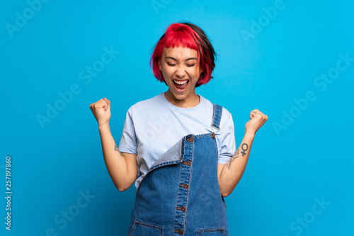 Fotografie, Obraz  Young woman with pink hair over blue wall celebrating a victory in winner positi