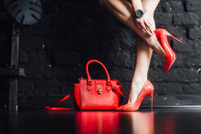 Female Legs In Red Maroon High Heel Shoes Goes On Black Background.