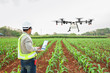 canvas print picture - Technician farmer use wifi computer control agriculture drone fly to sprayed fertilizer on corn fields, Smart farm 4.0 concept