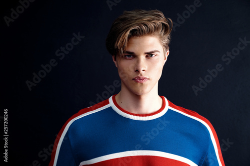 Obraz na plátne Serious handsome young man model wearing bright modern shirt looking at camera o