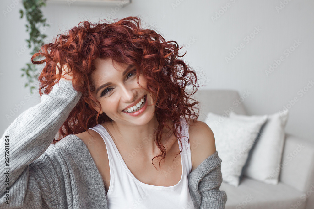 Fototapeta Very attractive young woman close up portrait. Beautiful female indoor. Curly haired lady. Red-haired girl. Redhead with wavy hair.