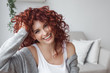 Very attractive young woman close up portrait. Beautiful female indoor. Curly haired lady. Red-haired girl. Redhead with wavy hair.