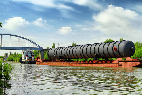 Fotografia  Heavy oversized chemical apparatus is transported by river transport through the
