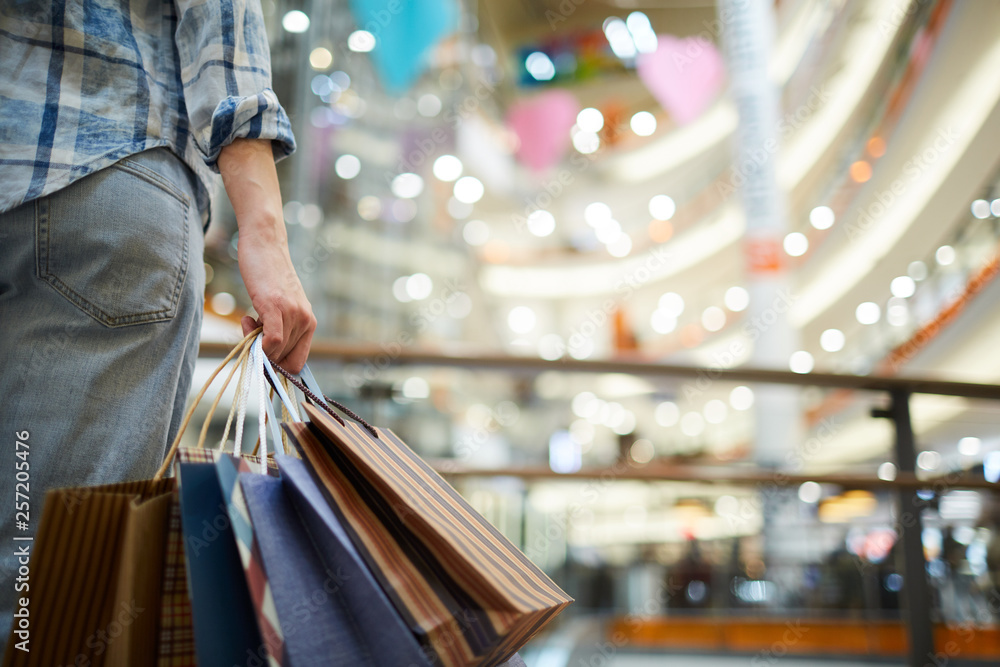 Fototapeta Close-up of unrecognizable woman in casual clothing standing in spacious shopping mall with lights and holding many paper bags