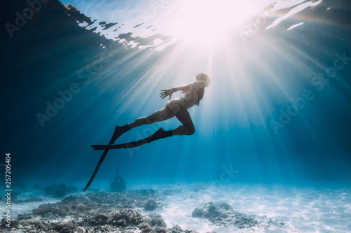 Fototapeta Freediver young woman with fins swim over sandy bottom underwater ocean obraz